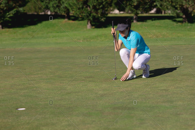 Caucasian woman playing golf placing ball before taking shot at hole. sport leisure hobbies golf healthy outdoor lifestyle.