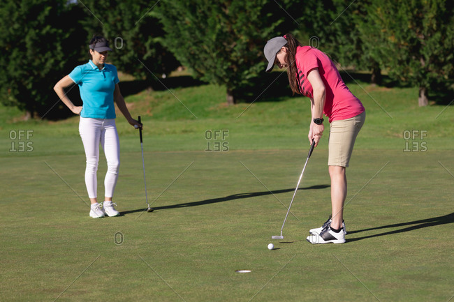 Two caucasian women playing golf one taking a shot at the hole. sport leisure hobbies golf healthy outdoor lifestyle.