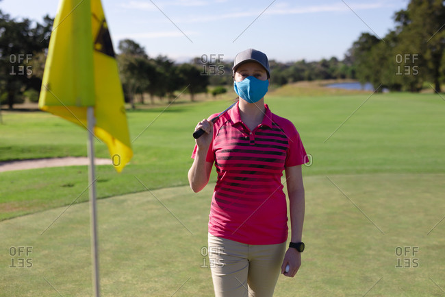 Portrait of caucasian woman wearing face mask holding club on golf course. sport leisure hobbies golf healthy outdoor lifestyle hygiene during coronavirus covid 19 pandemic.