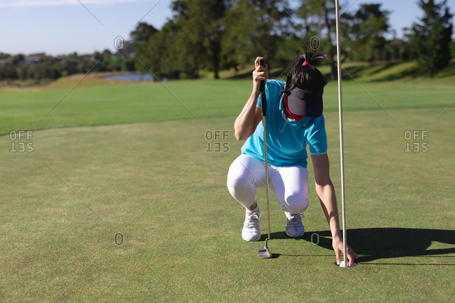 Caucasian woman wearing face mask taking ball from hole on golf course. sport leisure hobbies golf healthy outdoor lifestyle hygiene during coronavirus covid 19 pandemic.