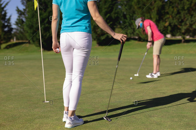 Two caucasian women wearing face masks playing golf one putting to the hole. sport leisure hobbies golf healthy outdoor lifestyle hygiene during coronavirus covid 19 pandemic.