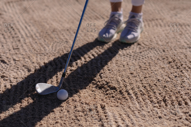 Low section of caucasian woman playing golf positioning club before taking shot from bunker. sport leisure hobbies golf healthy outdoor lifestyle.