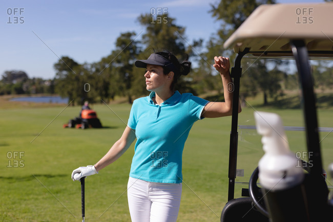 Caucasian woman playing golf leaning on golf cart at golf course. sport leisure hobbies golf healthy outdoor lifestyle.
