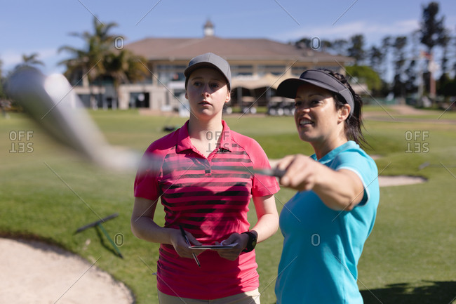 Two caucasian women playing golf talking one pointing with golf club. sport leisure hobbies golf healthy outdoor lifestyle.