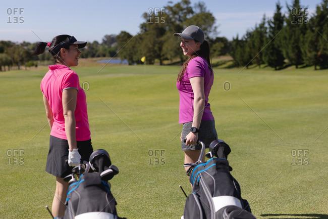 Two caucasian women walking across golf course talking pulling golf bags on wheels. sport leisure hobbies golf healthy outdoor lifestyle.