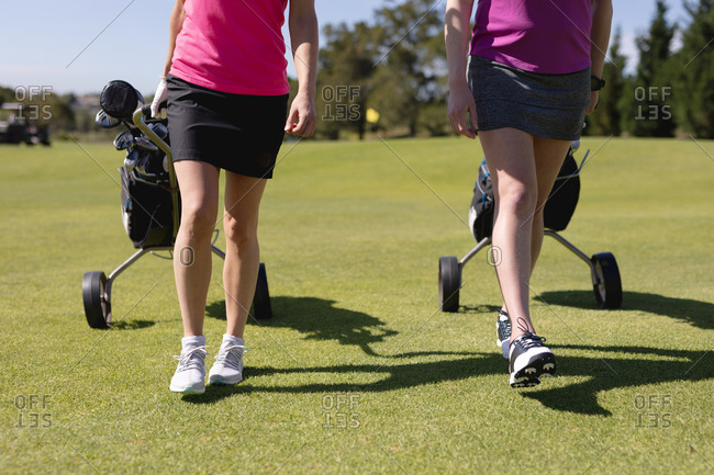 Low section of two caucasian women walking across golf course pulling golf bags on wheels. sport leisure hobbies golf healthy outdoor lifestyle.