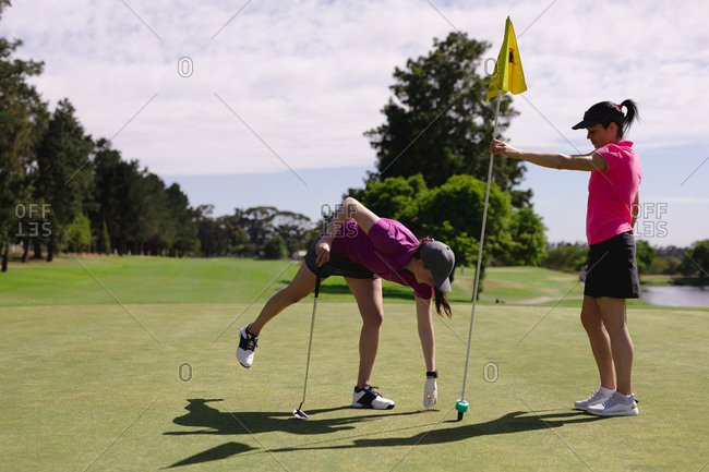 Two caucasian women playing golf one holding flag one taking ball from hole. sport leisure hobbies golf healthy outdoor lifestyle.