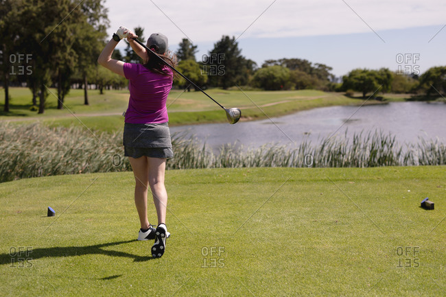 Caucasian woman playing golf swinging club and taking a shot. sport leisure hobbies golf healthy outdoor lifestyle.