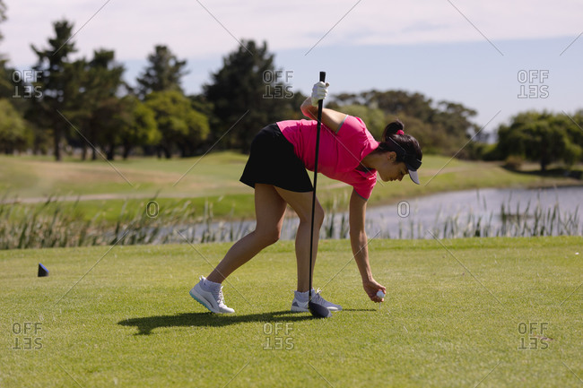 Caucasian woman playing golf leaning to place ball before taking a shot. sport leisure hobbies golf healthy outdoor lifestyle.