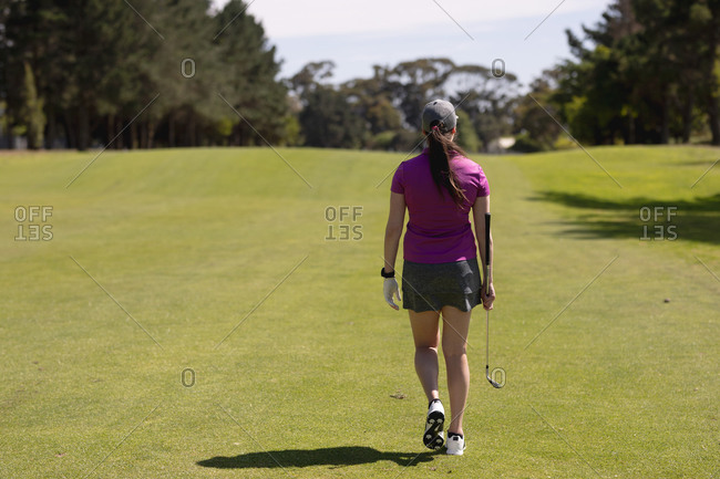 Rear view of caucasian woman holding golf club walking across golf course. sport leisure hobbies golf healthy outdoor lifestyle.