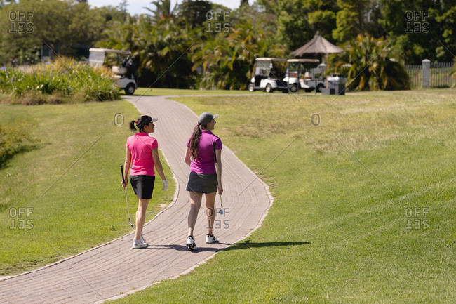 Two caucasian women playing golf walking on path at golf course. sport leisure hobbies golf healthy outdoor lifestyle.