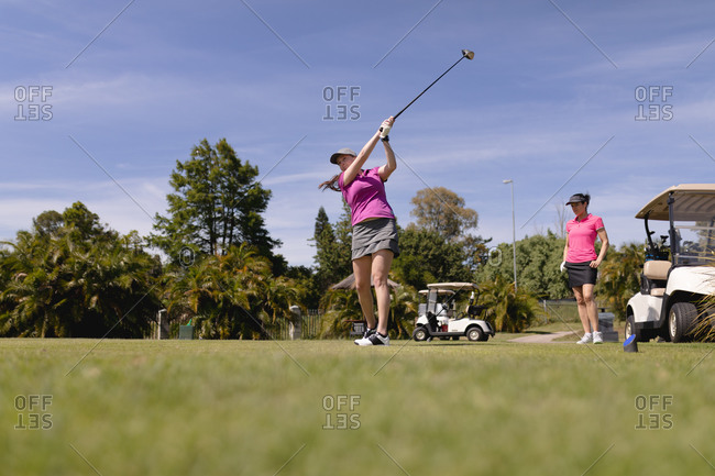 Two caucasian women playing golf one swinging club and taking a shot. sport leisure hobbies golf healthy outdoor lifestyle.