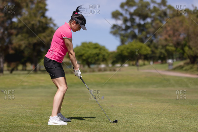Caucasian woman practicing golf at golf course on a bright sunny day. sports and active lifestyle concept.