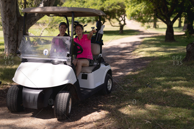 Two caucasian woman driving a golf cart with clubs on the back at golf course. sports and active lifestyle concept.