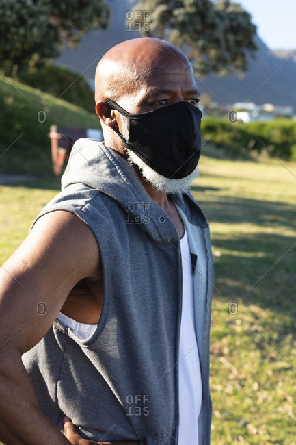 Senior African American man wearing face mask exercising outdoors. healthy retirement outdoor fitness lifestyle hygiene during coronavirus covid 19 pandemic.