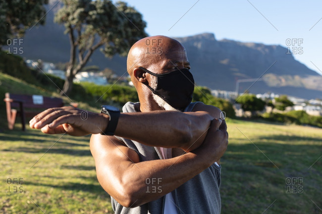 Fit senior African American man wearing face mask exercising outdoors stretching. healthy retirement outdoor fitness lifestyle hygiene during coronavirus covid 19 pandemic.