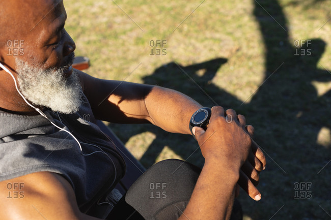 Fit senior African American man exercising wearing earphones checking smartwatch. healthy retirement technology communication outdoor fitness lifestyle.
