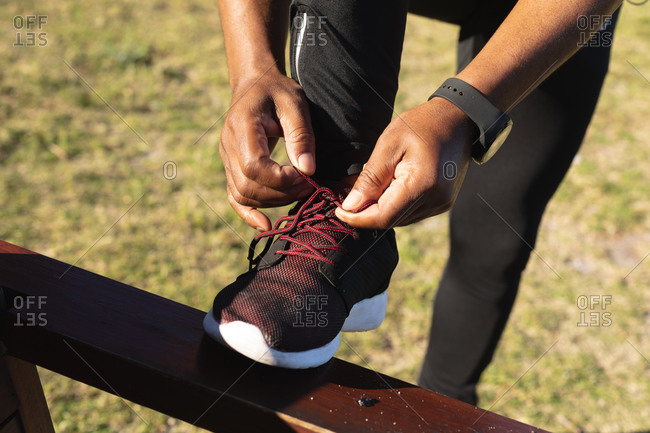 Low section of senior African American man exercising tying shoelaces. healthy retirement outdoor fitness lifestyle.
