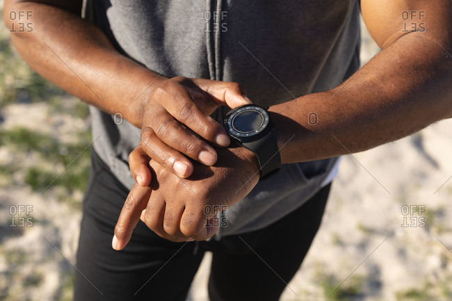 Mid section of fit African American man exercising checking smartwatch. healthy retirement technology communication outdoor fitness lifestyle.