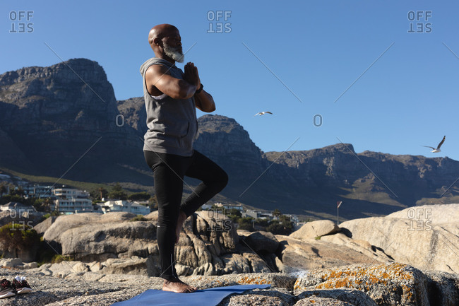 Fit senior African American man standing on rocky coast doing yoga. healthy retirement outdoor fitness lifestyle.
