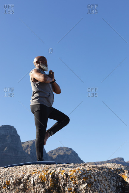 Fit senior African American man standing in pose doing yoga. healthy retirement outdoor fitness lifestyle.