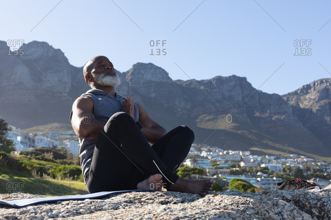 Fit senior African American man sitting on rock by mountain meditating. healthy retirement outdoor fitness lifestyle.