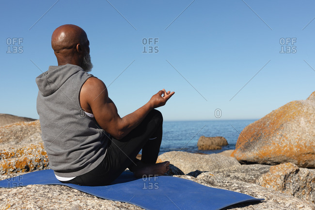 Fit senior African American man sitting on rocky coast meditating. healthy retirement outdoor fitness lifestyle.