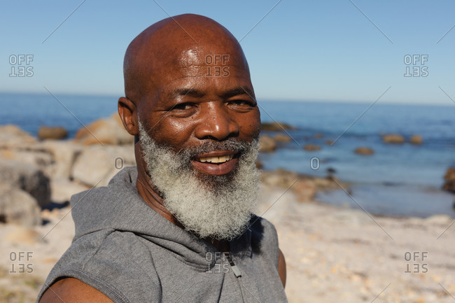 Portrait of fit senior African American man by the sea smiling. healthy retirement outdoor fitness lifestyle.