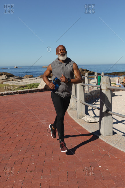 Fit senior African American man exercising running on coastal path. healthy retirement outdoor fitness lifestyle.