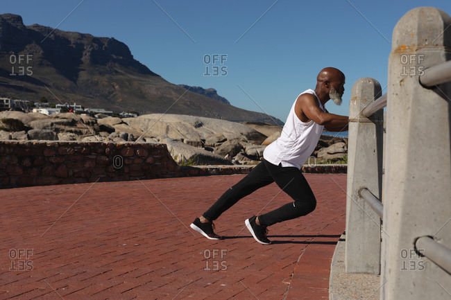 Fit senior African American man exercising leaning on fence stretching. healthy retirement outdoor fitness lifestyle.