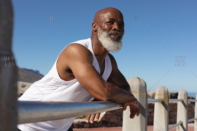 Fit senior African American man leaning on fence against blue sky. healthy retirement technology communication outdoor fitness lifestyle.