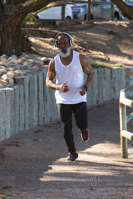 Midsection of fit senior African American man exercising running on path. healthy retirement outdoor fitness lifestyle.