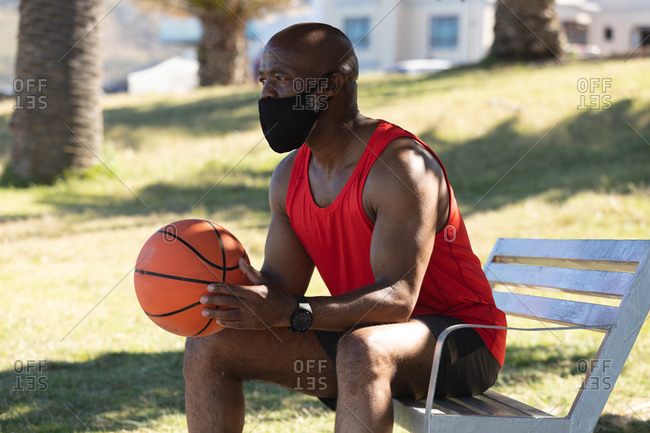 Fit senior African American man wearing face mask sitting in park holding basketball. healthy retirement outdoor fitness lifestyle hygiene during coronavirus covid 19 pandemic.