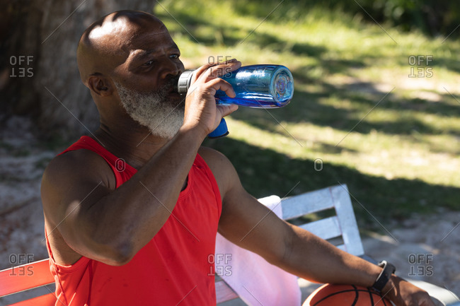 Fit senior African American man sitting in park drinking from water bottle. healthy retirement sport outdoor fitness lifestyle.