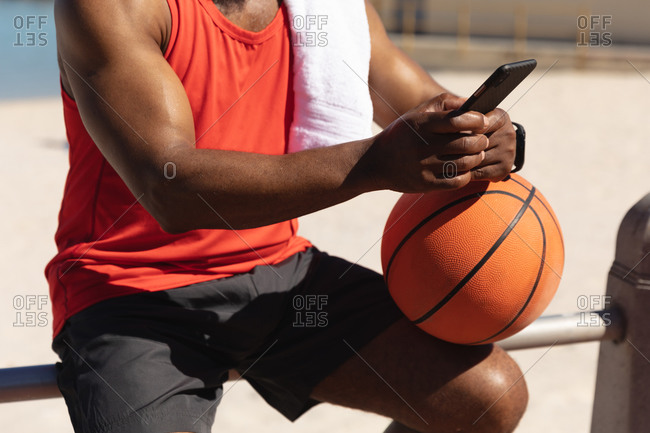 Midsection of fit senior African American man sitting in sun holding basketball using smartphone. healthy retirement technology communication outdoor fitness lifestyle.