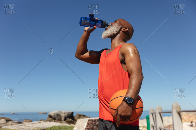 Fit senior African American man by sea drinking from water bottle holding basketball. healthy retirement sport outdoor fitness lifestyle.