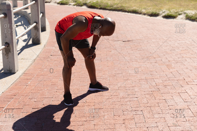 Fit senior African American man wearing earphones exercising in the sun catching his breath. healthy retirement sport outdoor fitness lifestyle.