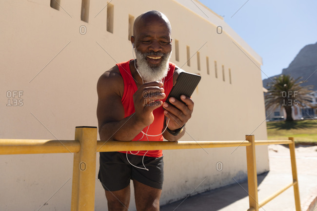 Fit senior African American man wearing earphones using smartphone in sunny street smiling. healthy retirement technology communication outdoor fitness lifestyle.