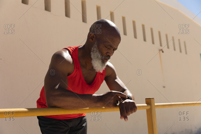Fit senior African American man exercising using smartwatch leaning on fence in sun. healthy retirement technology communication outdoor fitness lifestyle.
