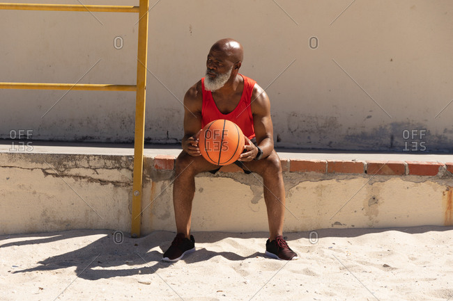 Fit senior African American man sitting on step in sun holding basketball. healthy retirement sport outdoor fitness lifestyle.