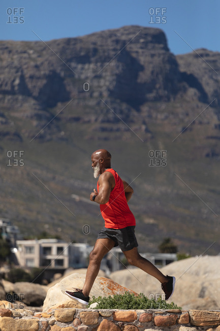 Fit senior African American man exercising running on rocky path beside mountain. healthy retirement outdoor fitness lifestyle.