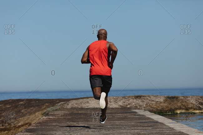 Rear view of fit senior African American man running on coastal path. healthy retirement outdoor fitness lifestyle.
