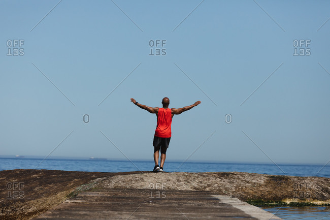 Rear view of fit senior African American man exercising by sea with arms outstretched. healthy retirement outdoor fitness lifestyle.