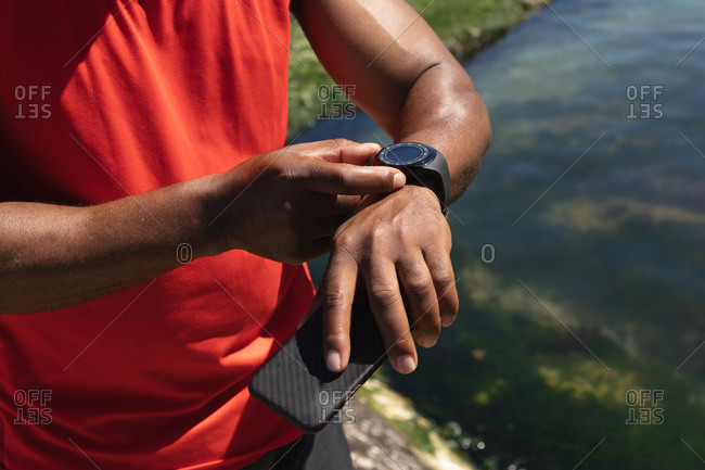 Midsection of fit African American man exercising using smartwatch in sun. healthy retirement technology communication outdoor fitness lifestyle.