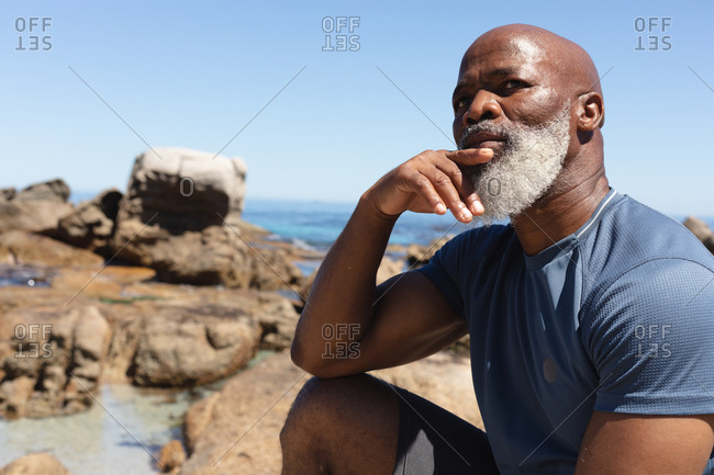 Fit senior African American man sitting on rocky coast thinking. healthy retirement outdoor fitness lifestyle.
