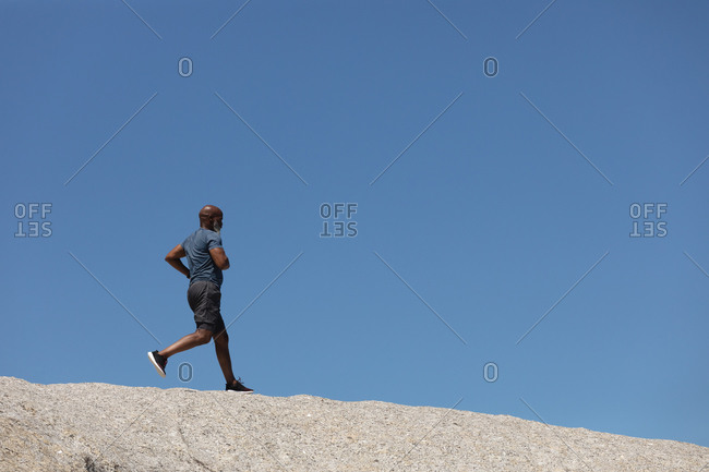 Fit senior African American man exercising running on rock against blue sky. healthy retirement outdoor fitness lifestyle.