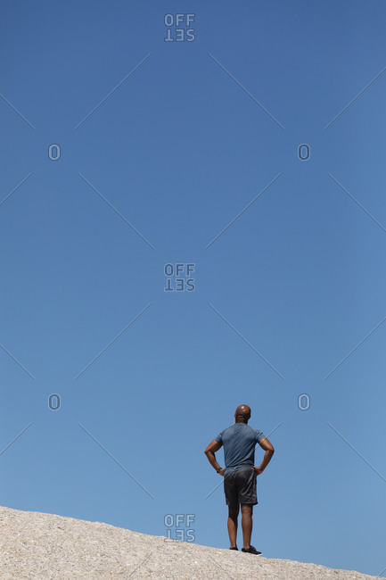 Rear view of fit senior African American man standing on rock against blue sky. healthy retirement outdoor fitness lifestyle.