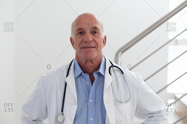 Portrait of senior caucasian male doctor looking at the camera and smiling. medical professional worker.