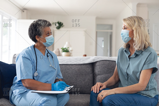 Senior African American female doctor talking with female patient both wearing face masks at home. healthcare hygiene protection during coronavirus covid 19 pandemic.