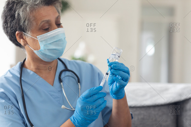 Senior African American female doctor wearing face mask preparing vaccination at home. healthcare hygiene protection during coronavirus covid 19 pandemic.